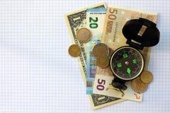 Composizione - soldi della bussola su un fondo a quadretti dello strato Fotografia Stock