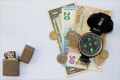Composizione - soldi della bussola su un fondo a quadretti dello strato più Fotografia Stock
