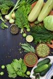 Composizione su un fondo scuro dei prodotti vegetariani organici verdi: legumi verdi, fagioli verdi, zucchini, aglio, cipolla Fotografie Stock
