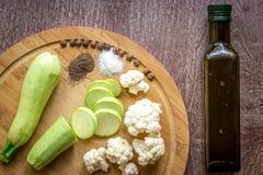 Composizione sugli alimenti vegetariani organici del fondo di legno: zucchini, cavolfiore, pepe nero e sale La vista da Immagini Stock Libere da Diritti