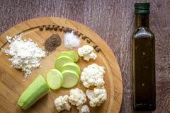 Composizione sugli alimenti vegetariani organici del fondo di legno: zucchini, cavolfiore, pepe nero, farina di frumento e sale Fotografie Stock Libere da Diritti