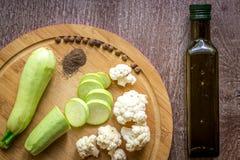 Composizione sugli alimenti vegetariani organici del fondo di legno: zucchini, cavolfiore, pepe nero La vista dalla parte superio Fotografia Stock Libera da Diritti
