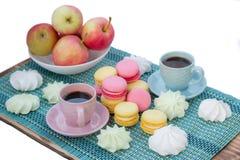 Composizione in tempo del caffè con le tazze, maccheroni, caramelle gommosa e molle, appl Fotografia Stock