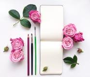 Composizione variopinta con lo sketchbook, le rose e le matite Disposizione piana Fotografie Stock