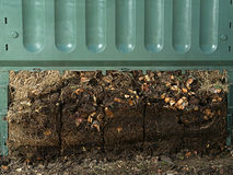 Compost bin. Closeup of green plastic compost bin with lower part removed to show advanced soil decomposition process Royalty Free Stock Photo