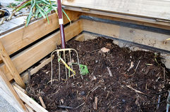 Compost bin with fork. Open compost bin with garden fork Royalty Free Stock Photo
