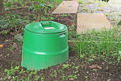 Compost bin in the garden. Compost bin made of recycled plastic next to vegetable garden. Recycling Stock Images