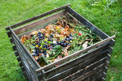 Compost bin. In the garden. Composting pile of rotting kitchen fruits and vegetable scraps Stock Image
