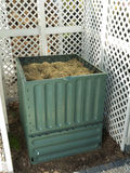 Compost bin. Green plastic compost bin full with lawn cut grass Stock Photography