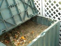 Compost bin. Green plastic compost bin full with lawn cut grass and domestic food scraps Stock Photo