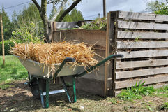 Compost bin  and wheelbarrow. Wooden compost bin for organic waste and wheelbarrow full of straw Stock Images