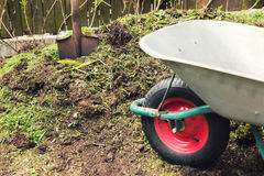 Compost - garden plant fertilizer. Wheelbarrow and spade Royalty Free Stock Photos