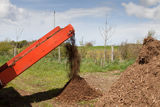 Compost Machinery Operating. Compost being driven out from a hopper with a belt tray into a pile ready for use Royalty Free Stock Photo