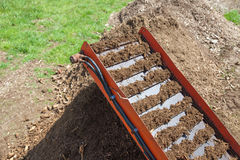 Compost Machinery Operating. Compost being driven out from a hopper with a belt tray into a pile ready for use Royalty Free Stock Image