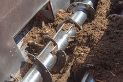 Compost Machinery Operating. Compost being turned and cut in a hopper or trailer. Large shaft and rotary blades doing the work of mulching the vegetation Stock Images