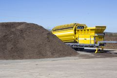 Compost. Pile of mulch at a green recycle plant ready to be fed into an industrial grinder to make compost Stock Image