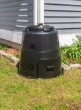 Composter noir au coin d'une maison photographie stock libre de droits