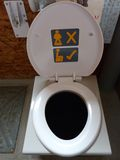 Composting toilet. Sit don't stand to pee in this environmentally friendly toilet Royalty Free Stock Photography