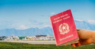 Composto di Digital della mano che tiene un passaporto italiano con il terminale di aeroporto occupato Immagini Stock