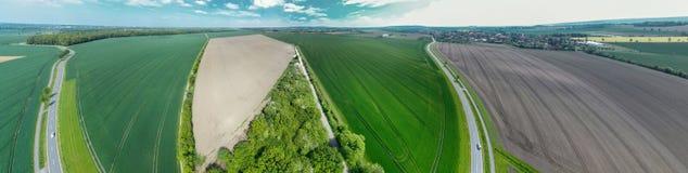 Composto panorama del cilindro da 360 gradi di una strada campestre che conduce attraverso i campi ed i prati ad un villaggio acc fotografia stock libera da diritti