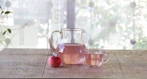 Compota de manzanas frescas en un jarro transparente en una tabla de madera Imagenes de archivo