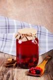 Compota deliciosa doce das bagas no frasco de vidro na tabela de madeira Foto de Stock Royalty Free