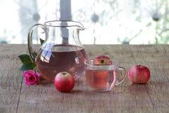 Compote της Apple φρέσκα μήλα στα διαφανή κανατών και και αυξήθηκε Στοκ φωτογραφία με δικαίωμα ελεύθερης χρήσης