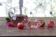 Compote της Apple φρέσκα μήλα στα διαφανή κανατών και και αυξήθηκε Στοκ Φωτογραφίες