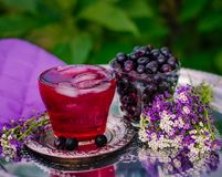 Compote of Aronia berries in the fresh air. fresh chokeberry berries in a glass stock images