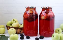Compote of berries and apples in jars on a table on a white background. stock photo