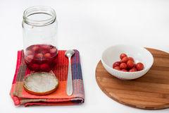 Compote of cherries in a jar with compote in a bowl on the kitch Royalty Free Stock Images