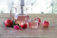 Compote from fresh apples in a transparent jug on a wooden table Royalty Free Stock Photography