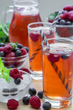 Compote of raspberries, strawberries and blueberries with straws. Royalty Free Stock Photos
