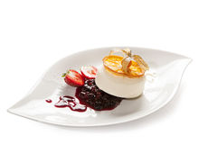 Compote with vanilla ice cream. Vanilla ice cream served with compote on a white plate decorated with various fruits and an orange slice caramelize , white Royalty Free Stock Photo