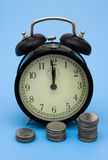 Compound interest. Coins with an old fashioned clock on a blue background, Compound interest Stock Photo
