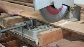 Compound miter saw cutting a piece of wood in carpentry workshop stock footage