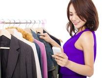 A compra asiática feliz da mulher veste-se com um telefone celular sobre o whi Foto de Stock Royalty Free