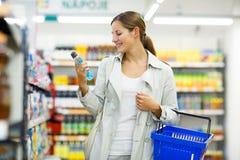 Compra bonita da jovem mulher em uma mercearia/supermercado foto de stock royalty free