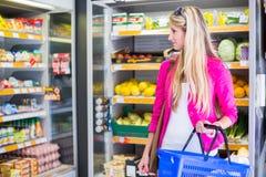 Compra bonita da jovem mulher em uma mercearia/supermercado Imagem de Stock