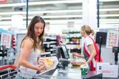 Compra bonita da jovem mulher em uma mercearia/supermercado Foto de Stock
