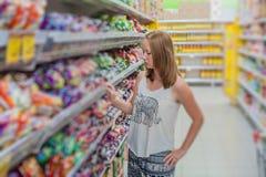 Compra bonita da jovem mulher para produtos do mantimento em um supermercado da mercearia Fotos de Stock Royalty Free