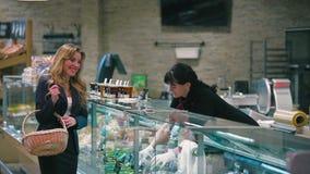Compra bonita da mulher as azeitonas no supermercado vídeos de arquivo
