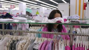 A compra bonita da mulher veste-se em ganchos no boutique filme