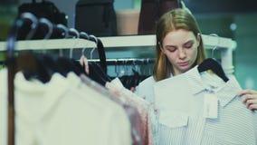A compra bonita da mulher veste-se em ganchos no boutique video estoque