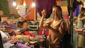 Compra chinesa da jovem mulher no mercado asiático da noite vídeos de arquivo