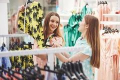 Compra com bestie Opinião traseira duas mulheres bonitas com os sacos de compras que olham a câmera com sorriso ao andar em foto de stock