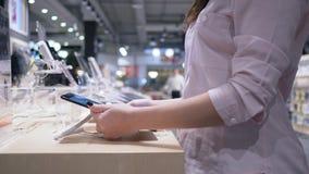 A compra, comprador vê o tablet pc o mais atrasado moderno na venda da exposição na loja da eletrônica filme