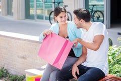 Compra da família Acople o assento em um banco e guardar a compra Imagem de Stock Royalty Free