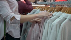 A compra da forma, as mãos fêmeas está escolhendo a roupa nova à moda em ganchos na loja durante descontos e a tentativa sazonais vídeos de arquivo