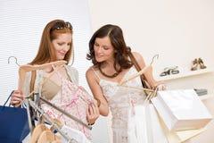 Compra da forma - a mulher dois feliz escolhe a roupa fotografia de stock